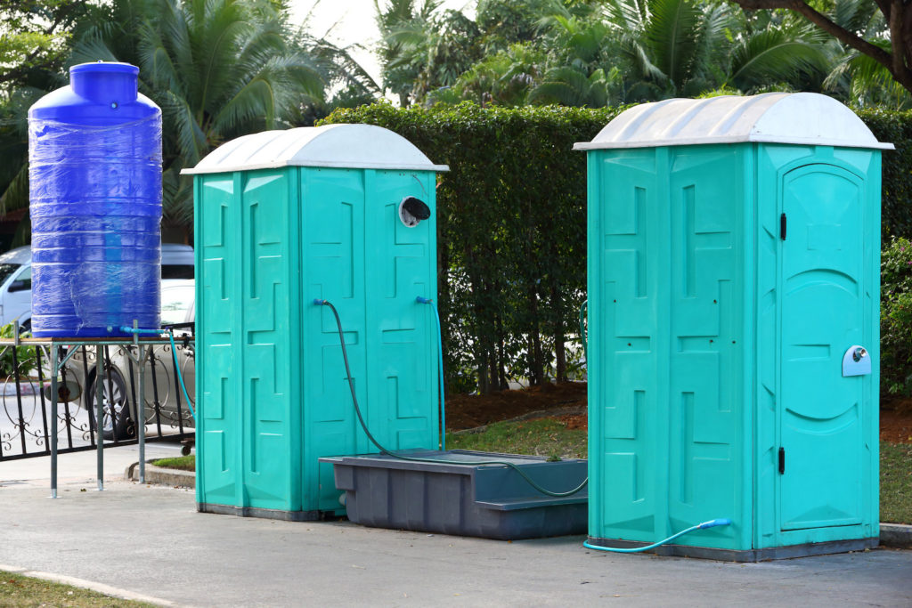 Green color Portable toilet with blue color water tank ready to service people for outdoor event
